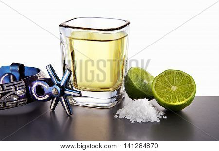 Tequila shot lemon and salt in a table with spurs