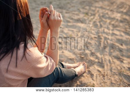 bootless woman sitting on beach at sunset; barefoot female on sand;