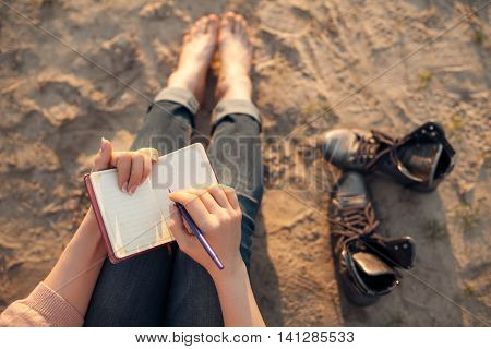 Female Makes Notes And Sitting On The Beach;