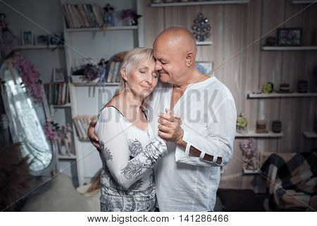 cheerful seniors couple embrace and smile; older male and female in love;