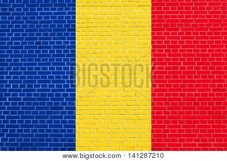 Flag of Romania on brick wall texture background. Romanian national flag.