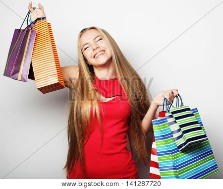 Portrait of young happy smiling woman with shopping bags, over white background