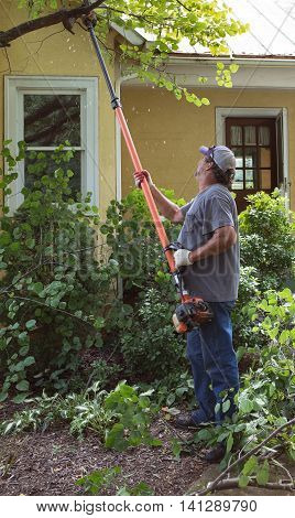 Man cutting tree branches in front of a yellow house