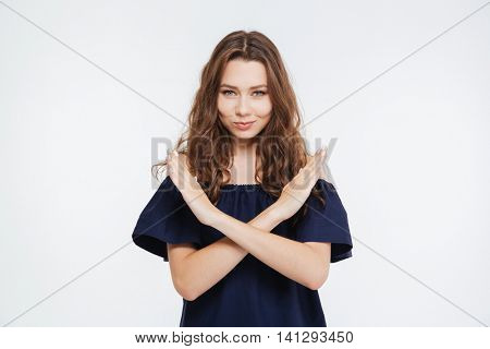Attractive young woman standing with hands crossed and showing stop gesture over white background