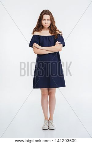 Full length of angry pretty young woman standing with arms crossed over white background