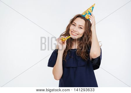 Cheerful young woman in birthday hat with party whistle over white background