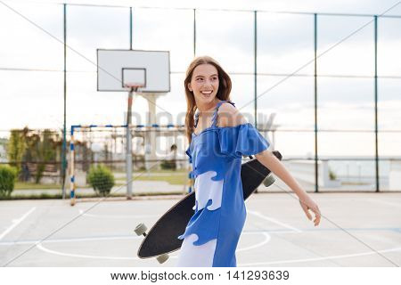 Portrait of a laughing female skater walking and looking away outdoors