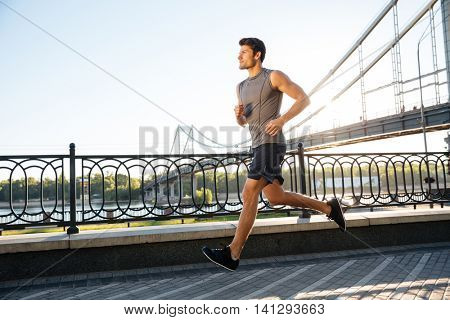 Side view of a handsome sports man running fast along big modern bridge at sunset light