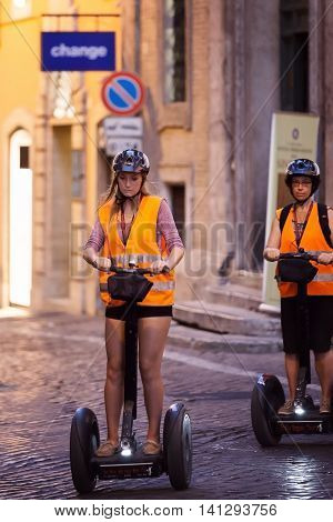 Rome Italy - August 3 2016: Two girls pass through the narrow streets of the city center with the help of a modern segway.