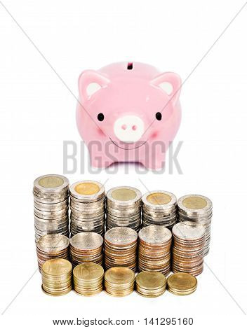 Money coins tower and pink piggybank isolated on white background.