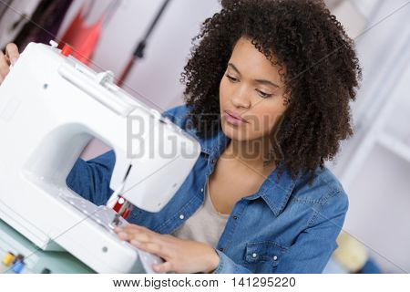 young woman sewing fabric on sewing machine