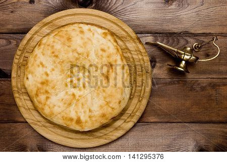 Traditional Uzbek bread and a lamp on a wooden background