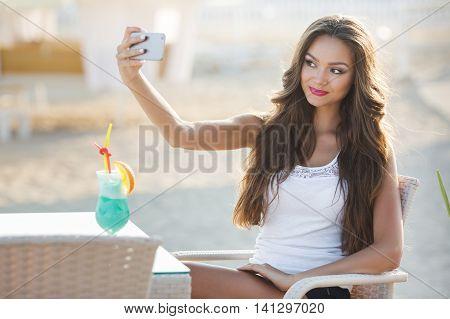 Closeup portrait young beatiful girl taking photo selfie on smart phone.