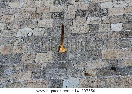 A medieval castle arrow slit in the historic wall of Old Jerusalem, Israel.