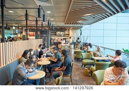 SINGAPORE - CIRCA NOVEMBER, 2015: customers in Starbucks at Singapore Changi Airport. Starbucks Corporation is an American global coffee company and coffeehouse chain.