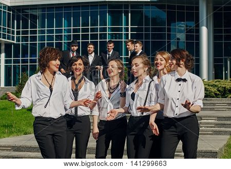 cheerful friends dressed tuxedo in the summer city. women have talk on first plan and men on second plan. there is modern building behind