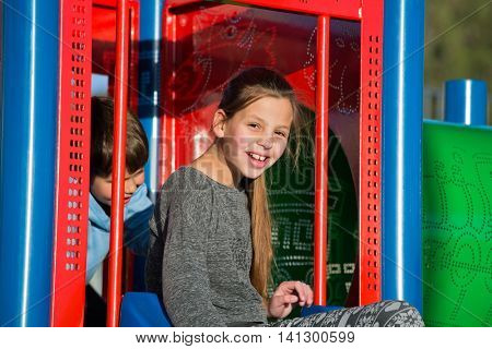 Lovely kids on the playground. Older sister and younger brother in the children's slides