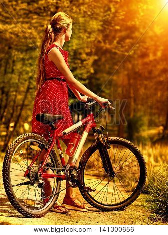 Girl with bicycle. Girl wearing sundress rides bicycle into park have rest. Girl in autumn park. Bicycle girl look away. Back view.