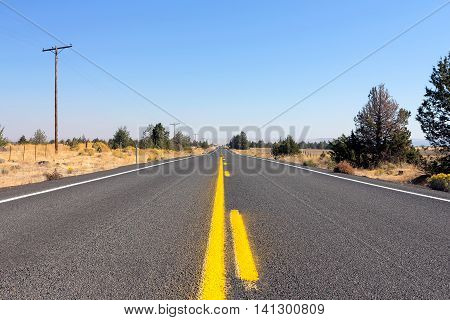 Middle of the Highway in rural farmland Central Oregon low perspective