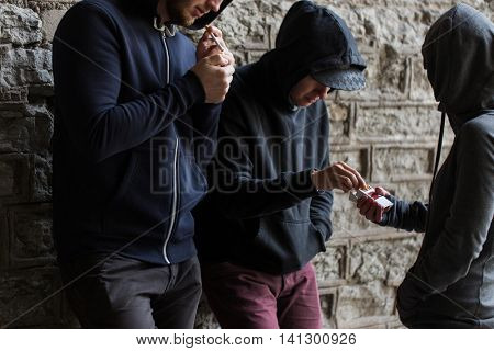 substance abuse, addiction, people and bad habits concept - close up of young smoking cigarettes outdoors