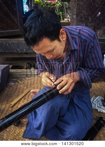 Bagan, Myanmar- December 2015 - A man demonstrates drawing patterns on a lacquer, Bagan, Mandalay, Myanmar