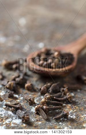 Cloves : Spice in wooden spoon on texture background