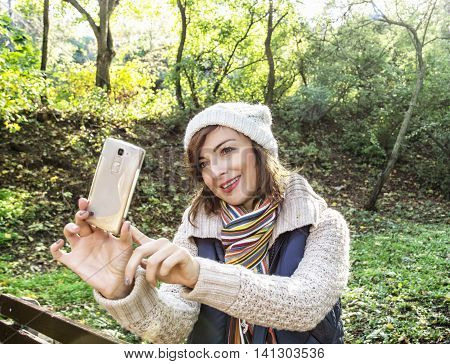 Beautiful young caucasian woman take the selfie photo in autumn nature. Beauty and fashion. Positive emotions. Female portrait.
