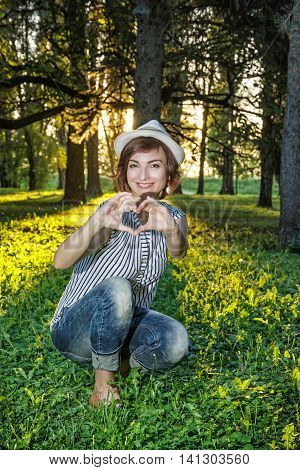 Young caucasian natural woman making heart shape in sunny backlight. Sexy female portrait. Big trees green grass and long shadows. Vertical composition.