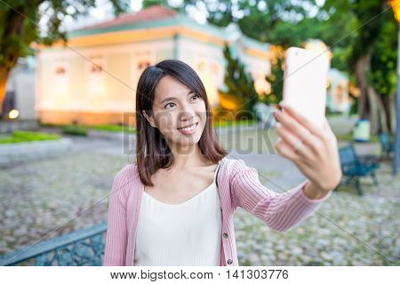 Woman taking selfie by smart phone in Taipa of Macao