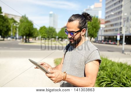 travel, tourism, backpacking, technology and people concept - man traveling with backpack and tablet pc computer in city searching location