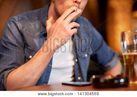 people, nicotine addiction and bad habits concept - close up of man drinking beer and smoking cigarette at bar or pub