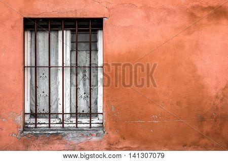 Old typical Mediterranean window on ocher stucco wall.