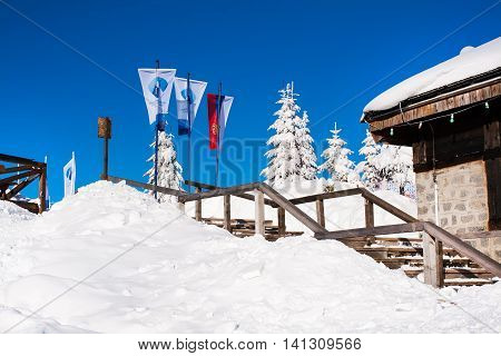 Kopaonik, Serbia - January 19, 2016: Serbian and ski resort flags on snowy mountain with trees background