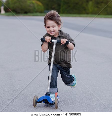 Happy little boy on scooter outdoors, square