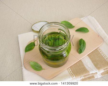 Homemade basil oil in jar and basil leaves