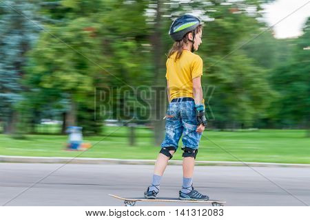 young boy skateboarding on natural background