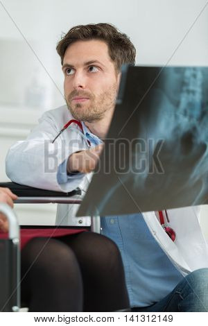 confident looking young doctor examining the results of a scan