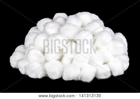 Pile of white cotton balls isolated against a black background