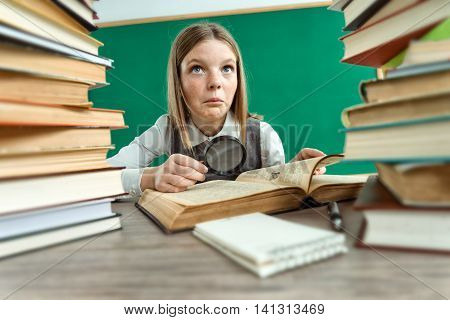 Beautiful girl doubts about read / photo of teen school girl wearing glasses creative concept with Back to school theme