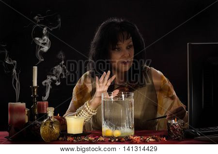 Fortune teller reading a shapes of separated egg whites into jar water. Black haired old female seer works in internet in front of a monitor