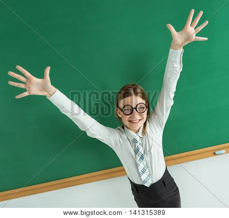 Humorous high angle view of Thrilled pupil raise her palms up / photo of teen school girl wearing glasses creative concept with Back to school theme