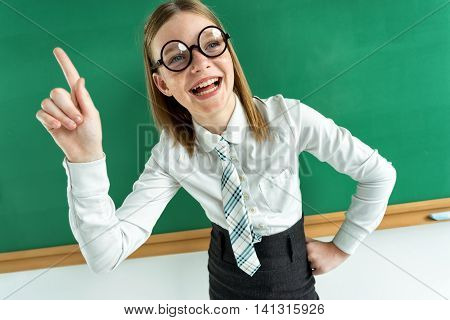 Cheerful enthusiastic pupil pointing with her finger up telling the teacher know something