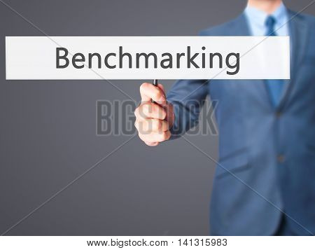 Benchmarking - Businessman Hand Holding Sign