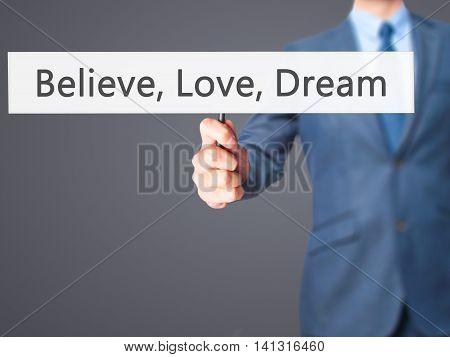 Believe, Love, Dream - Businessman Hand Holding Sign