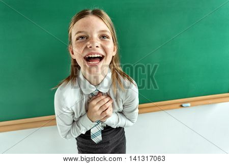 Humorous high angle view of Happy joyful laughing beautiful girl with hands clasped together