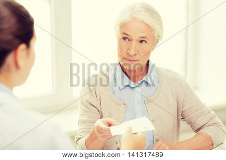 medicine, age, health care and people concept - doctor giving prescription to senior woman at hospital