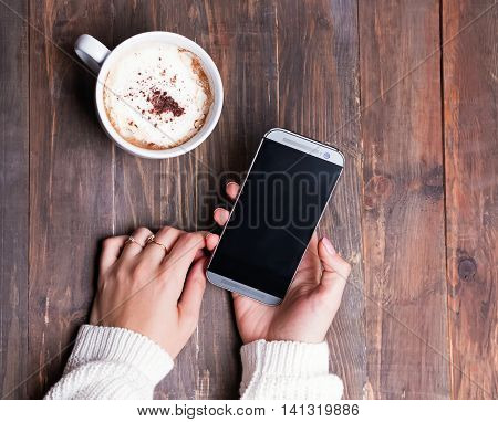Woman's hands holding smartphone and cup of coffee on wooden table