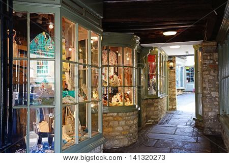 BURFORD, UNITED KINGDOM - JULY 20, 2016 - Small shops in a traditional old shopping arcade along The Hill shopping street Burford Oxfordshire England UK Western Europe, July 20, 2016.