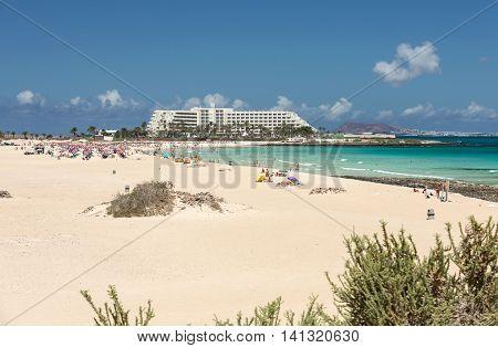 FUERTEVENTURA, SPAIN - SEPTEMBER 17, 2015: Tourists rest on Corralejo Beach on Fuerteventura Canary Islands
