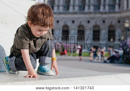 Little boy playing on city square, horizontal